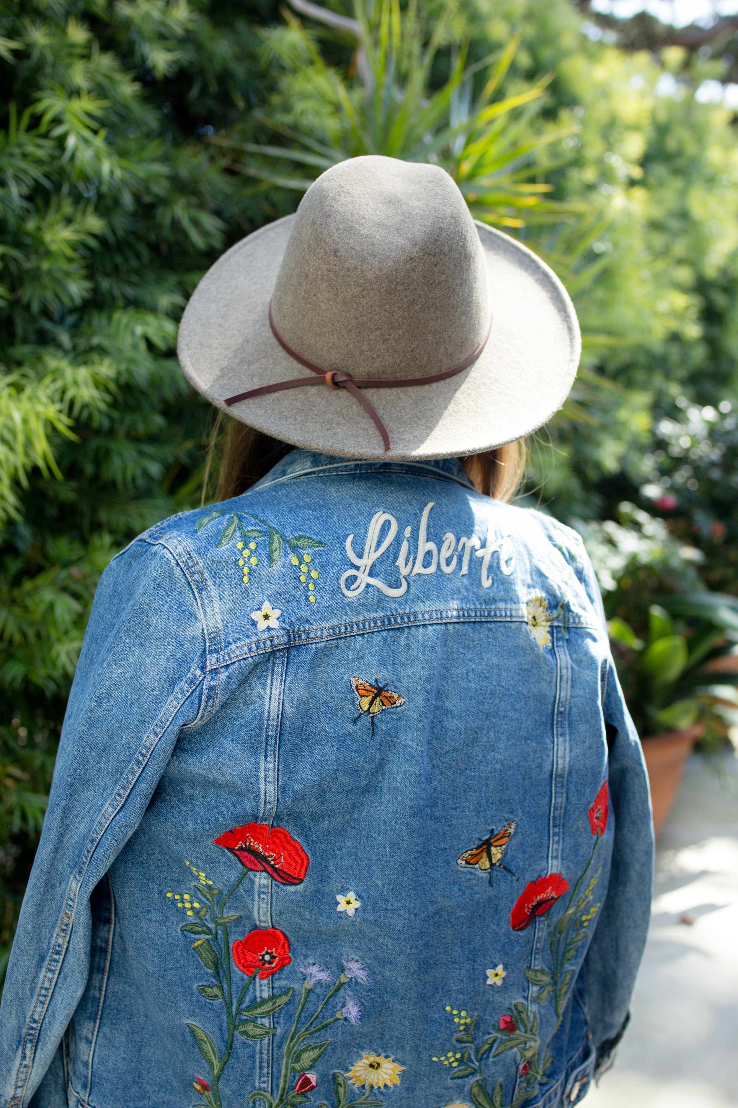 Girl wearing H&M Embroidered Denim Jacket and UO Structured Brim Felt Panama Hat infant of palm leaves