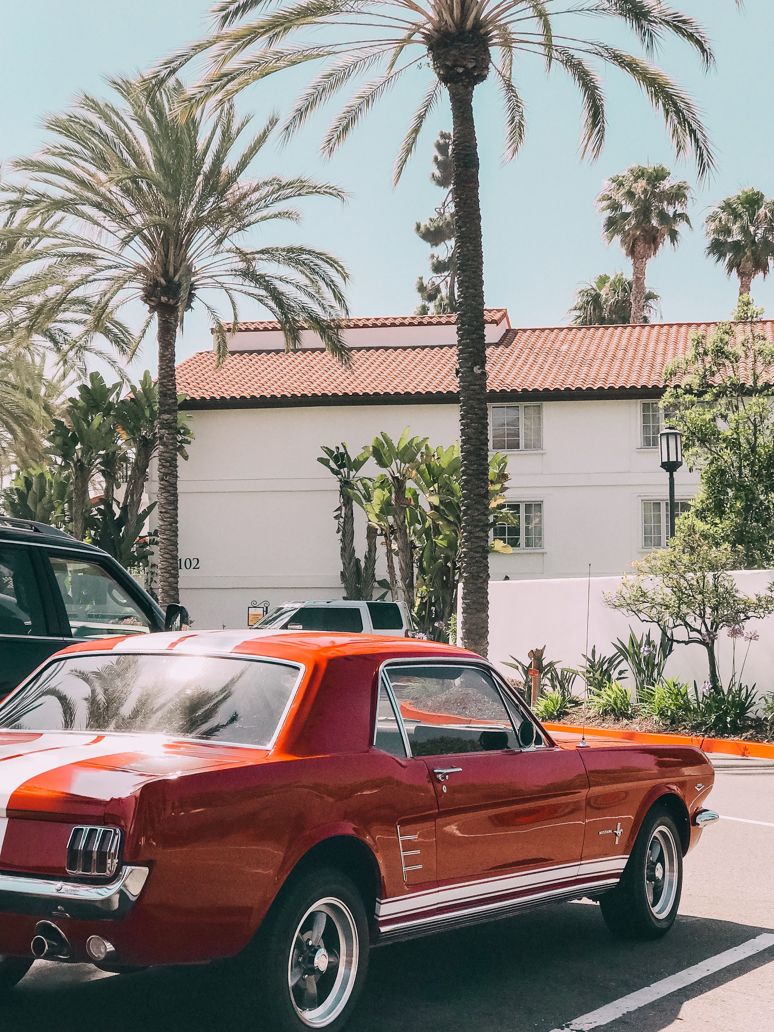 Vintage red mustang parked outside the Omni La Costa Resort & Spa
