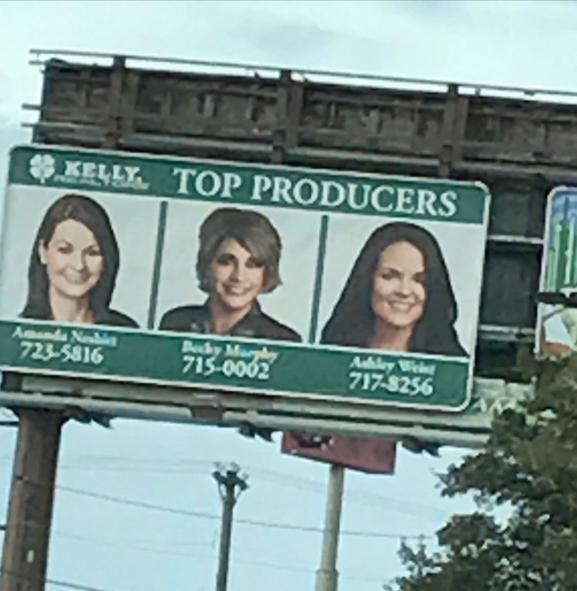 Owner of Sign This Custom Signs and Design featured (center) as a Kelly, Realtors Top Producer!