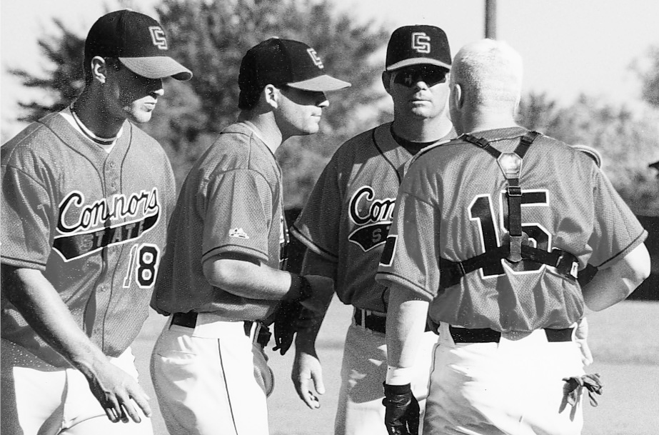 Coach Keith huddles with members of the Cowboys baseball team, 2000.