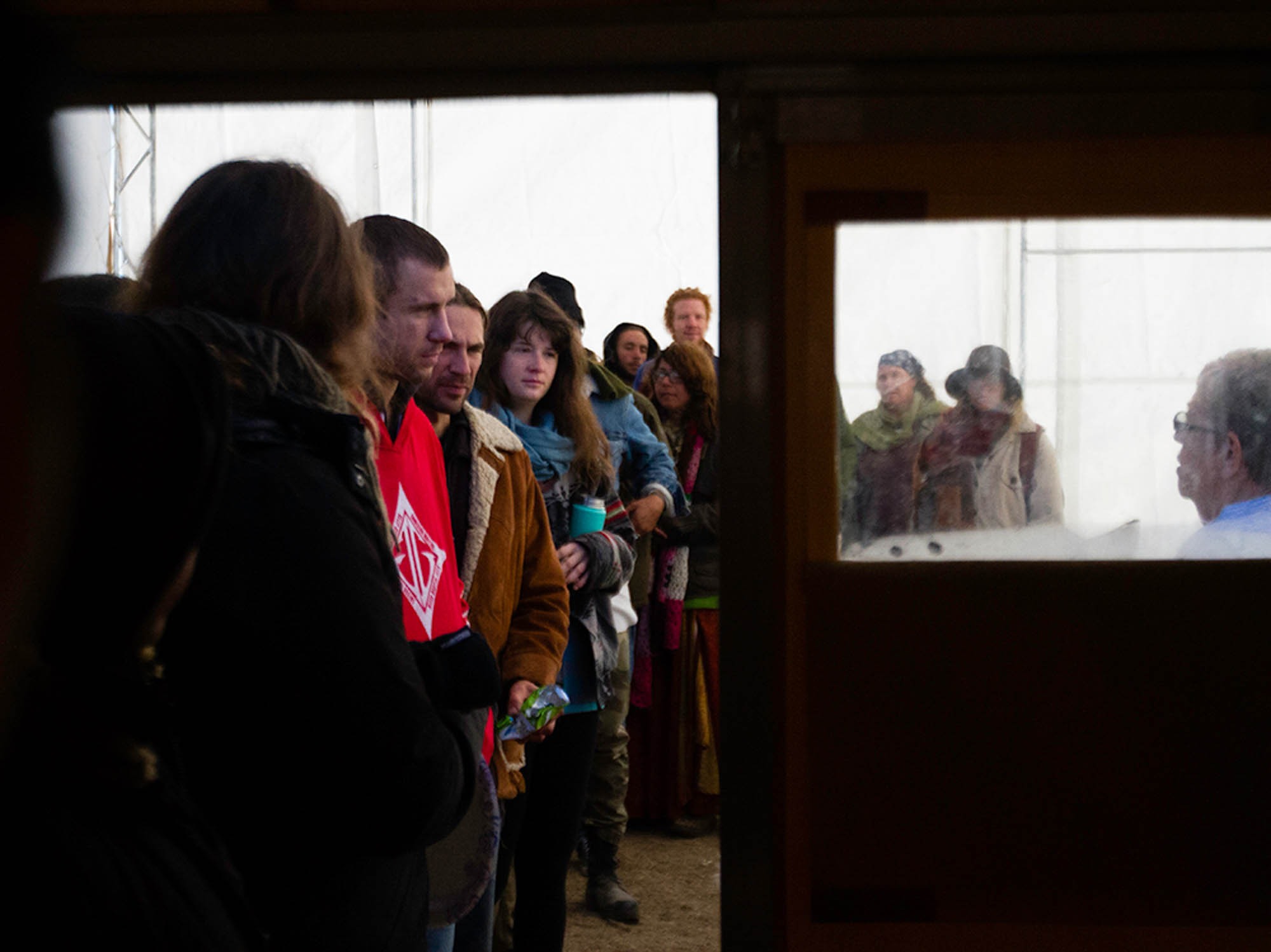 Campers at the Oceti Sakowin wait in line for breakfast at one of the few kitchens in the campsite.