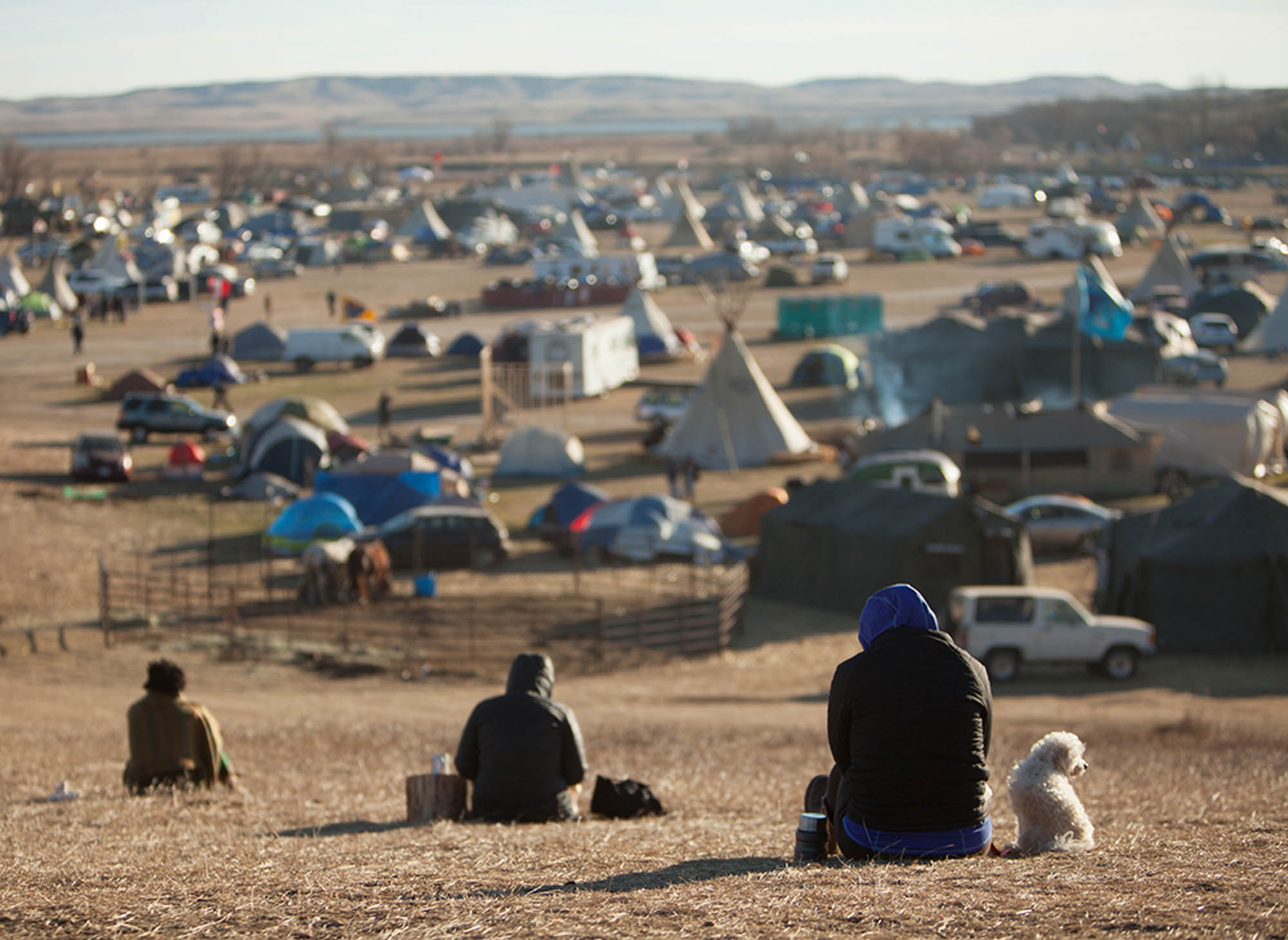 Protesters look over the Standing Rock protest site on a hill dubbed 'media hill'. 'Media hill' was one of the few places in the area cell phones were able to get reception and was often puncuated with people making calls and checking social media.