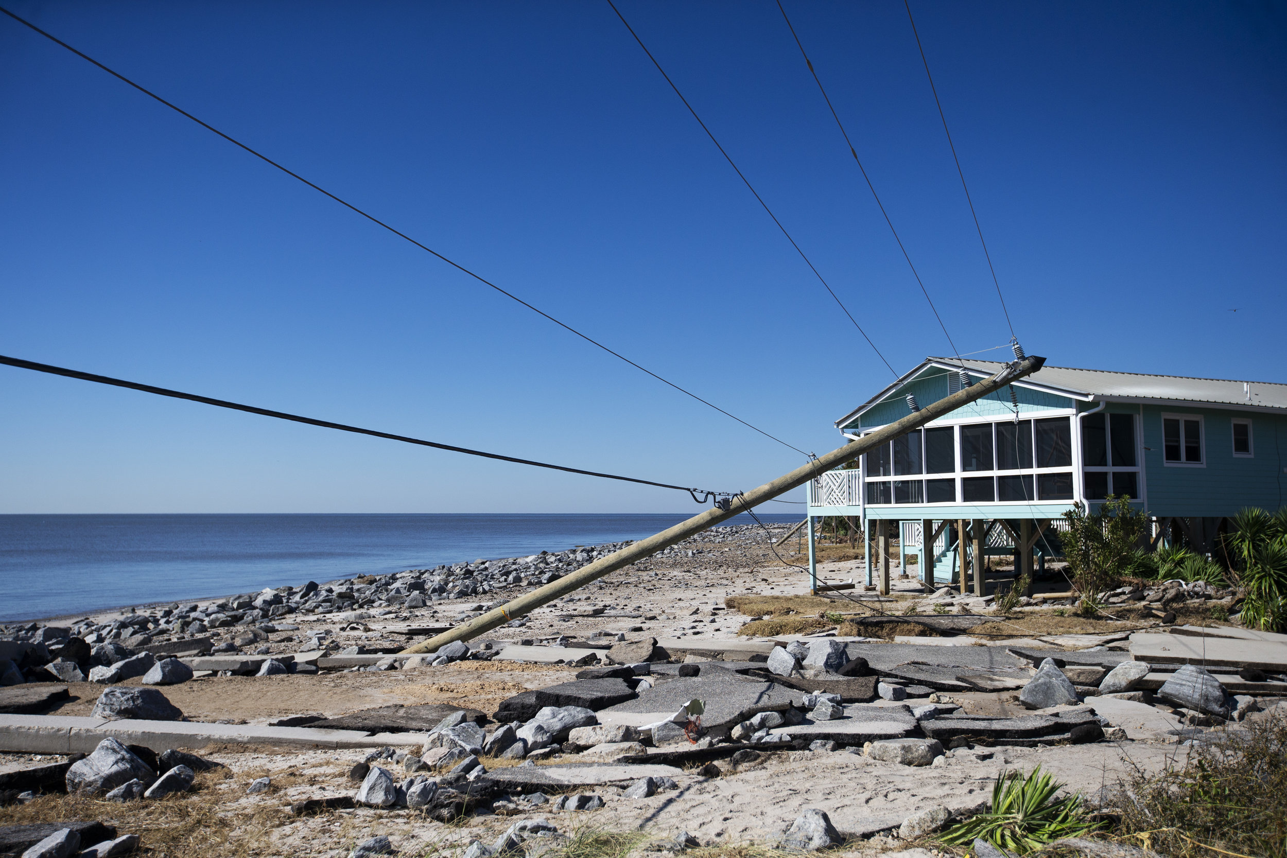 Downed powerlines lean into homes on Alligator Drive in Alligator Point on October 12, 2018.