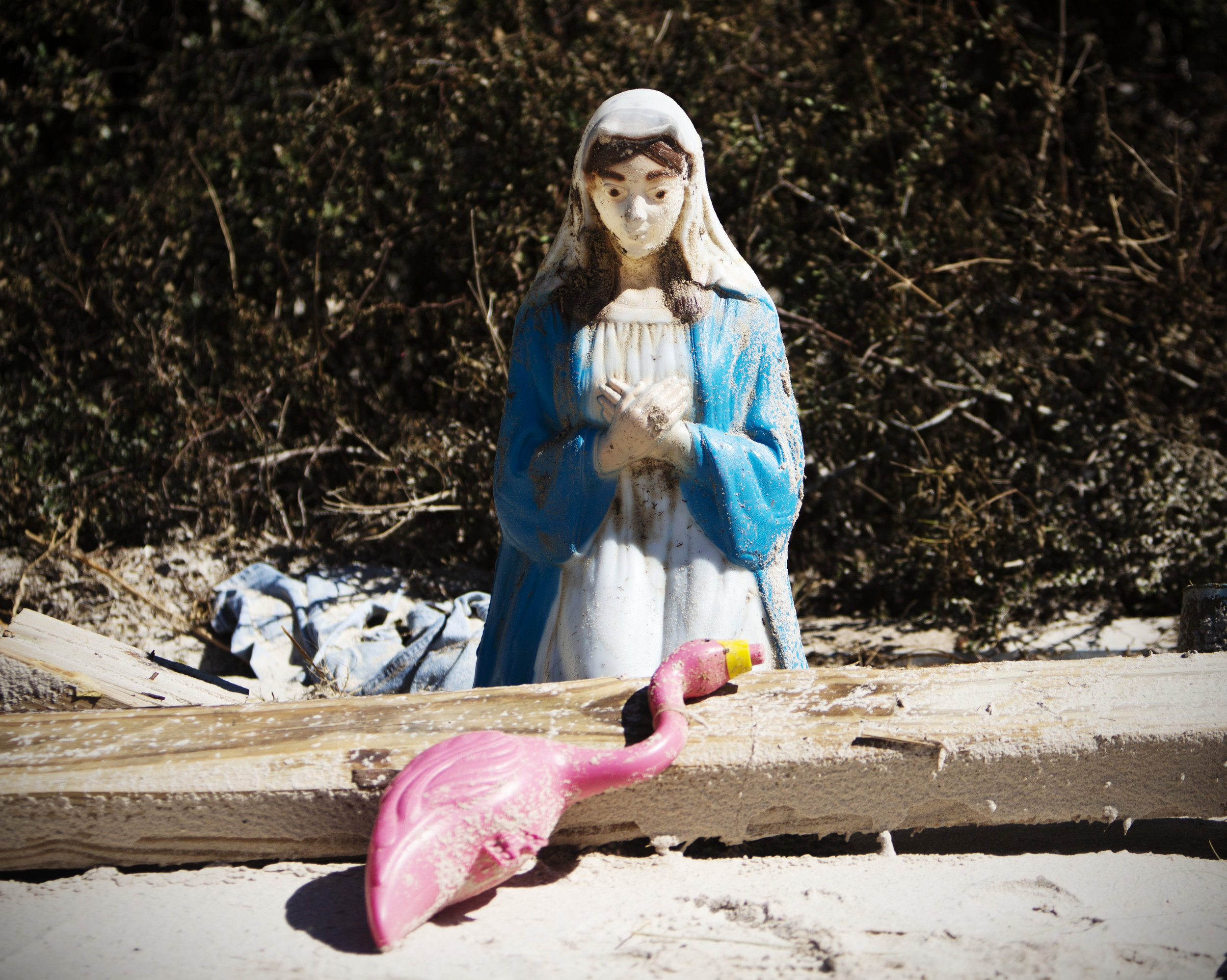 A Virgin Mary sits over a plastic flamingo near debris on Alligator Drive in Alligator Point on October 12, 2018.