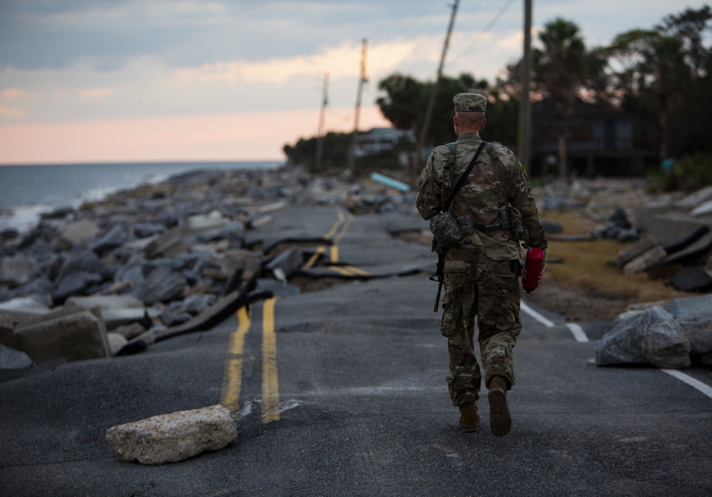 Florida Army National Guard Lt. Matt Wagner walks along what is left of Alligator Drive in Alligator Point on October 11, 2018, one day after Hurricane Michael hit the area. The National Guard descended on the area around 4 p.m..