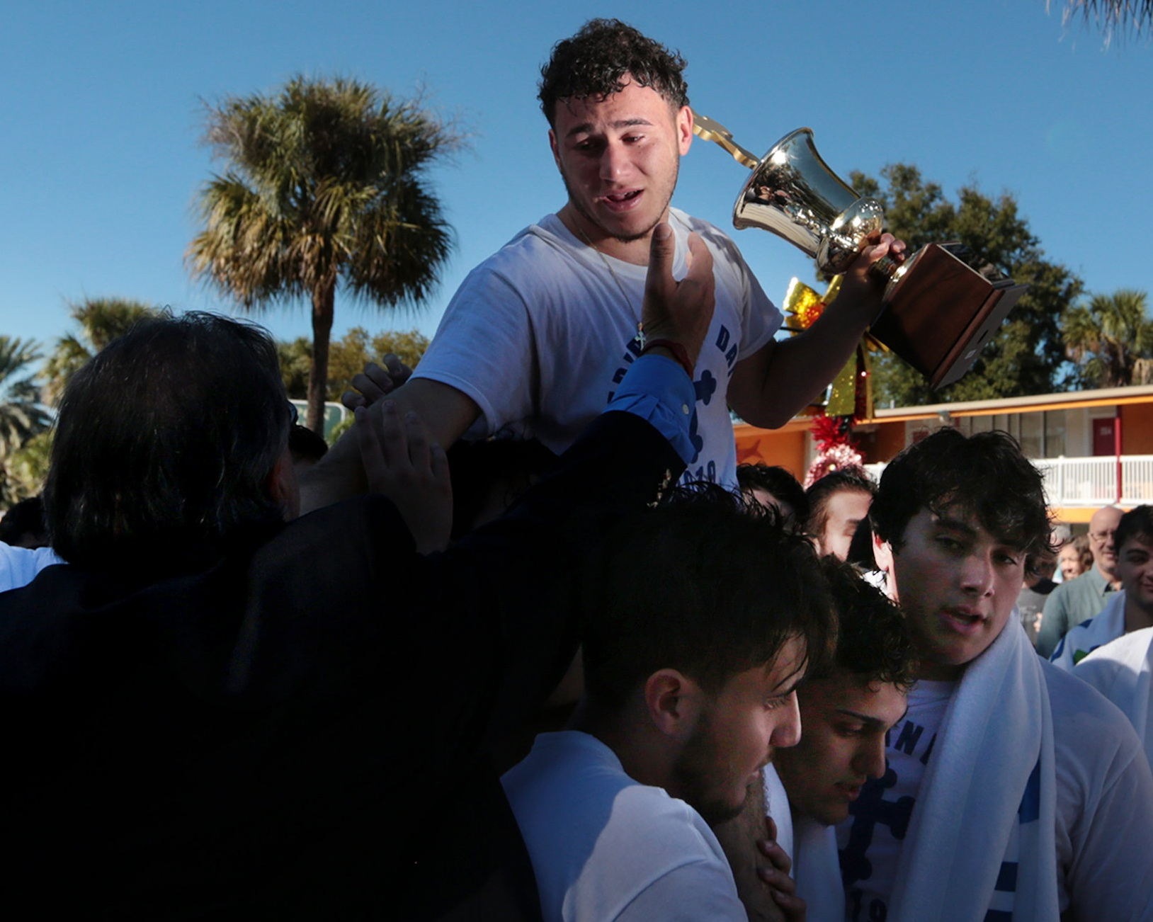 Cross retriever Ilias Skandaliaris, 17, of Tarpon Springs, reaches into the crowd as he is carried by fellow cross divers to the Saint Nicholas Greek Orthodox Church during Epiphany at Spring Bayou in Tarpon Springs, Florida on Sunday, January 6, 2019. The celebration in Tarpon Springs is often called the largest Epiphany celebration in the Western Hemisphere.