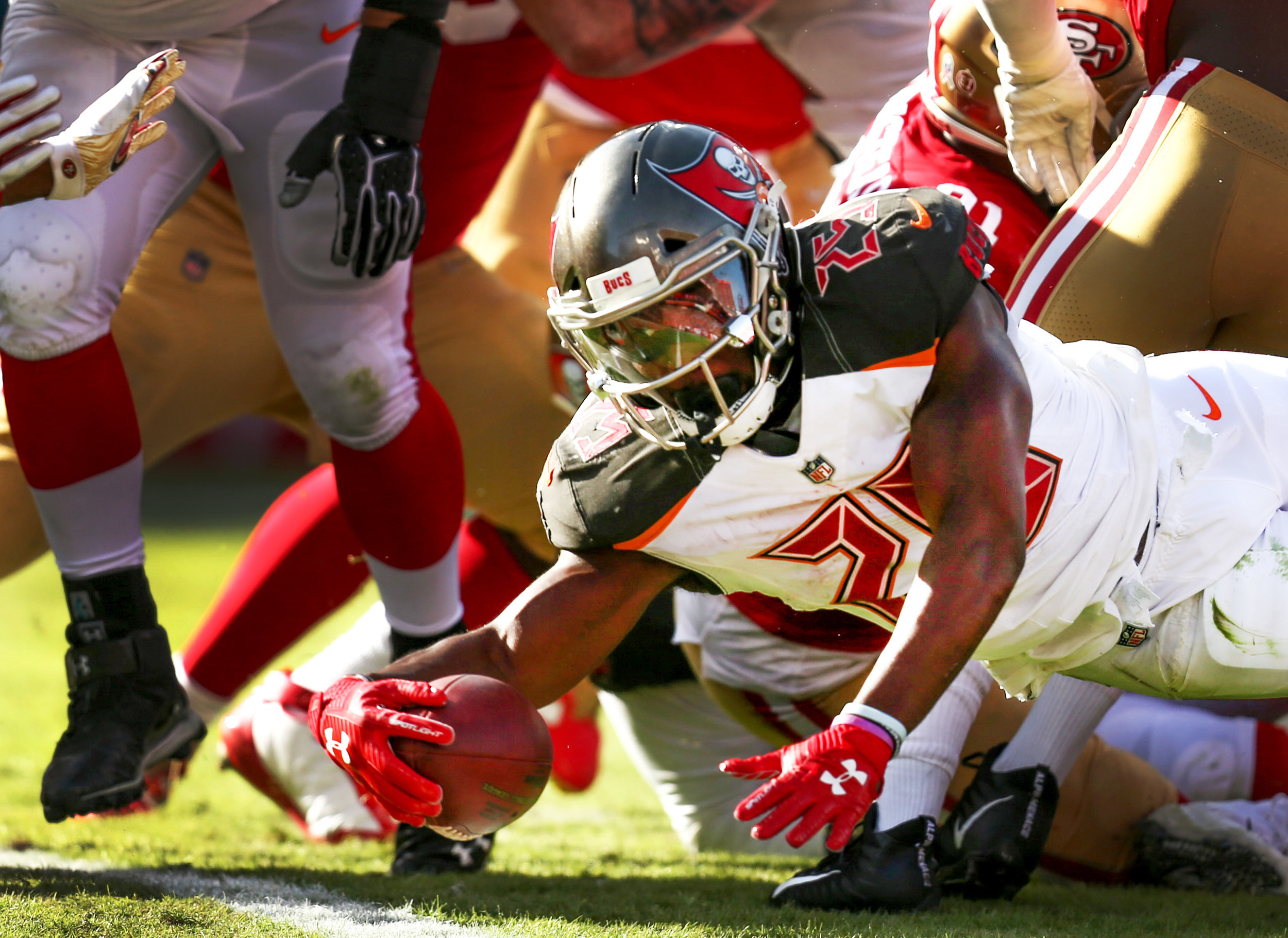Tampa Bay Buccaneers running back Peyton Barber (25) pushes through the defense to land a touchdown during the third quarter of the Tampa Bay Buccaneers game against the San Francisco 49ers on November 25, 2018 at Raymond James Stadium in Tampa, Fla.