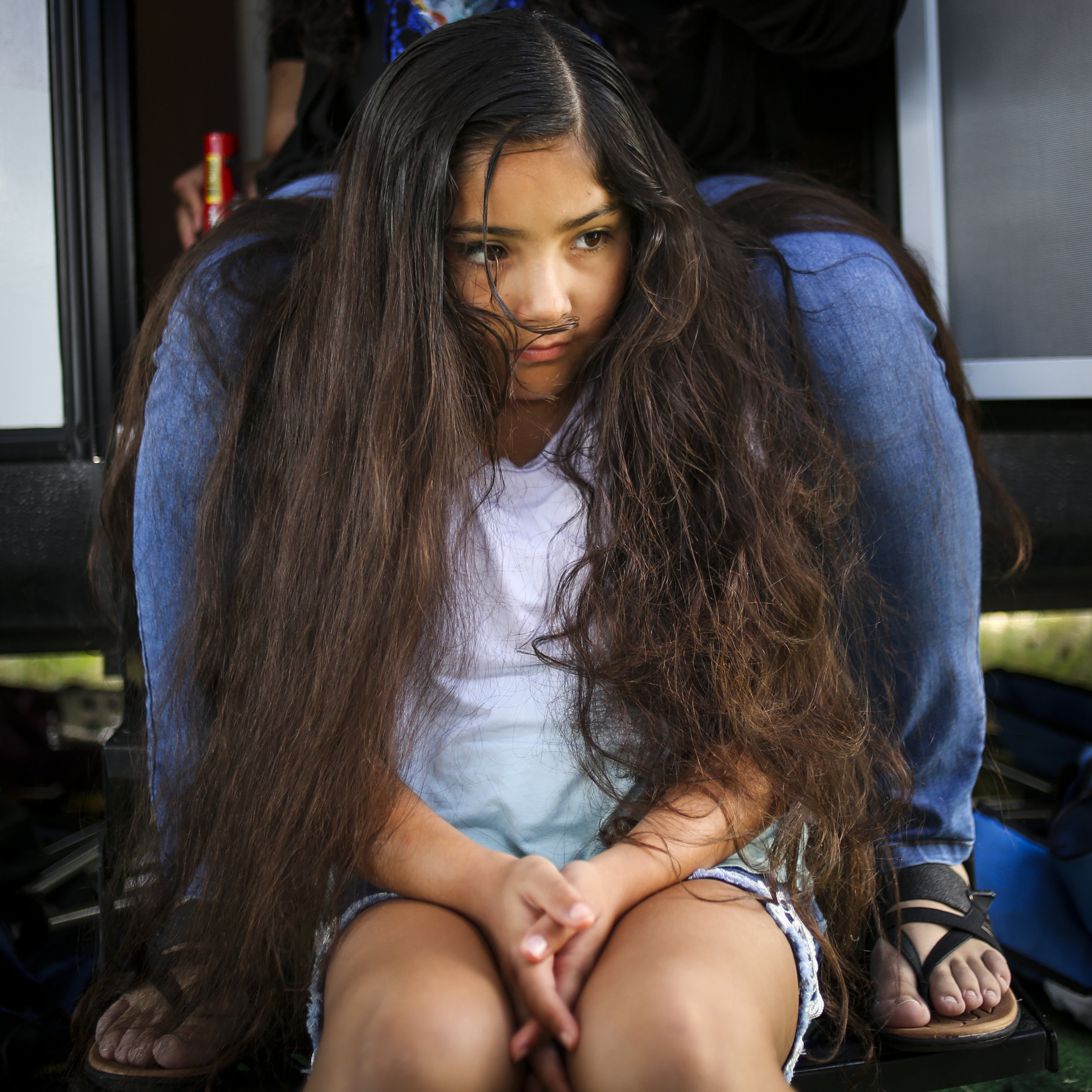 Esther Montoya, 8, sits between her mother's legs on the stairs of their camper waiting for her hair to be braided at the 121st Arlee Celebration in Arlee, Montana on July 4, 2019. Hair is just the first step in the long process of getting prepared to dance.