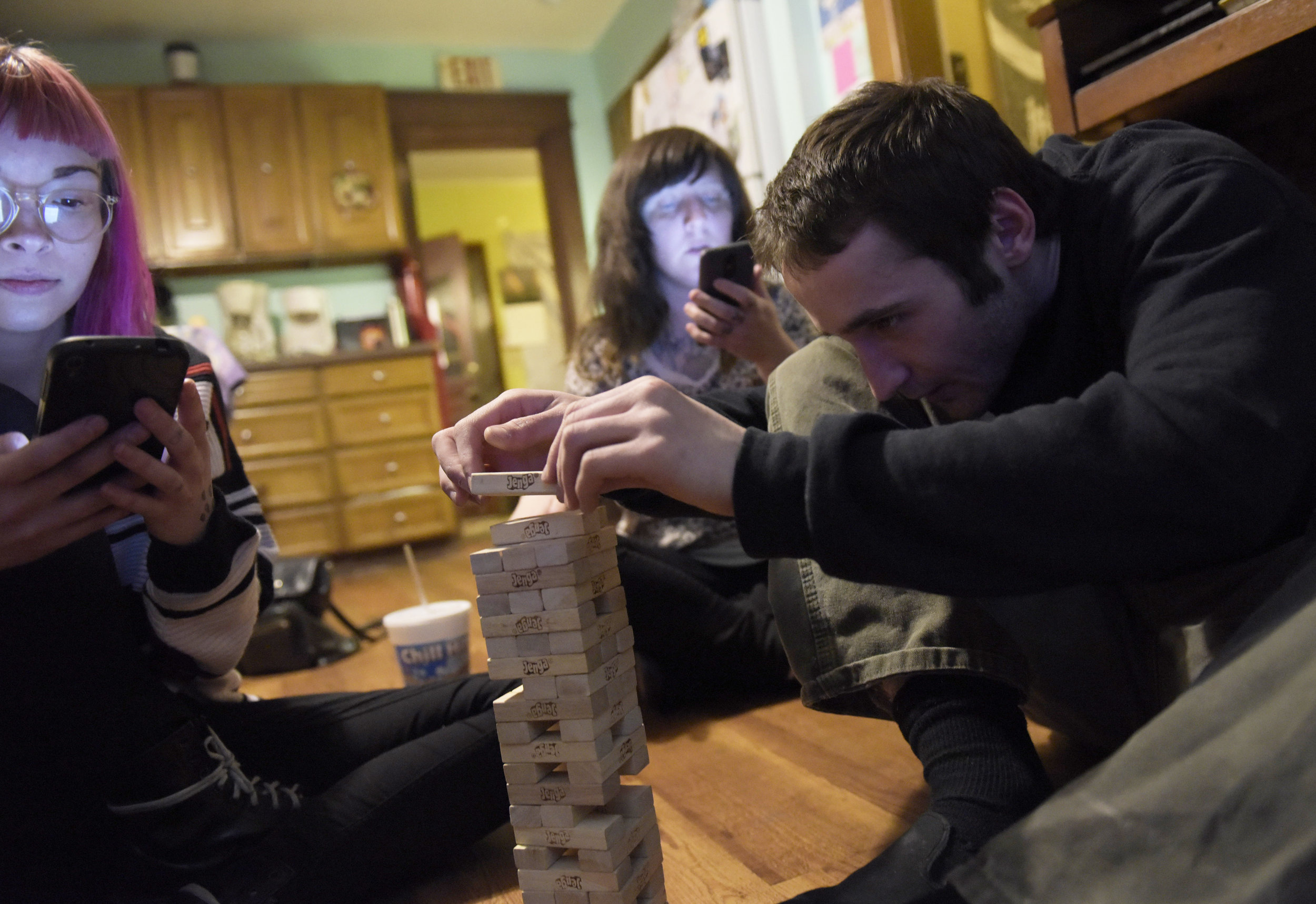 "(From left) Briana, Alyssa and George play Jenga one evening. At this point, Alyssa had been sober for five weeks. Before getting sober, she was throwing up blood and blacking out multiple times a week. A doctor told her that she has a genetic disease she inherited from her mother and if she didn't stop drinking, she would be throwing up blood for the rest of her life. Alyssa is thankful that giving up alcohol hasn't been as hard as she thought and she is appreciative of her friends' support. ""I wouldn't be as healthy I am without the people I surround myself with."""