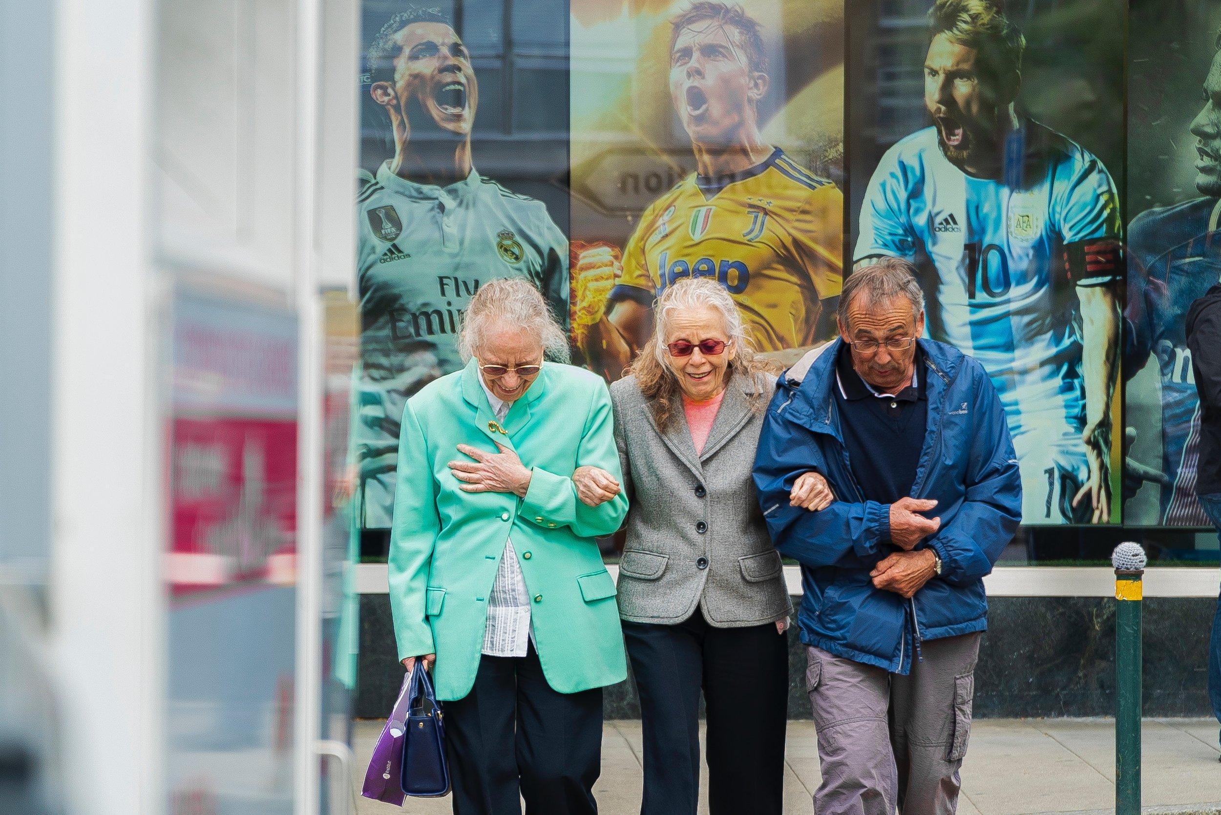 Happy elderly friends walking down the street