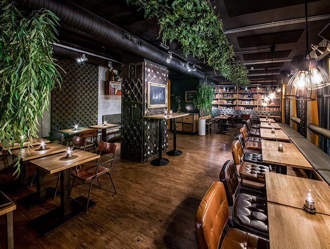 På Nedre Løkka blir du møtt med varme lys, høye lounge sofaer og et rustikt design.