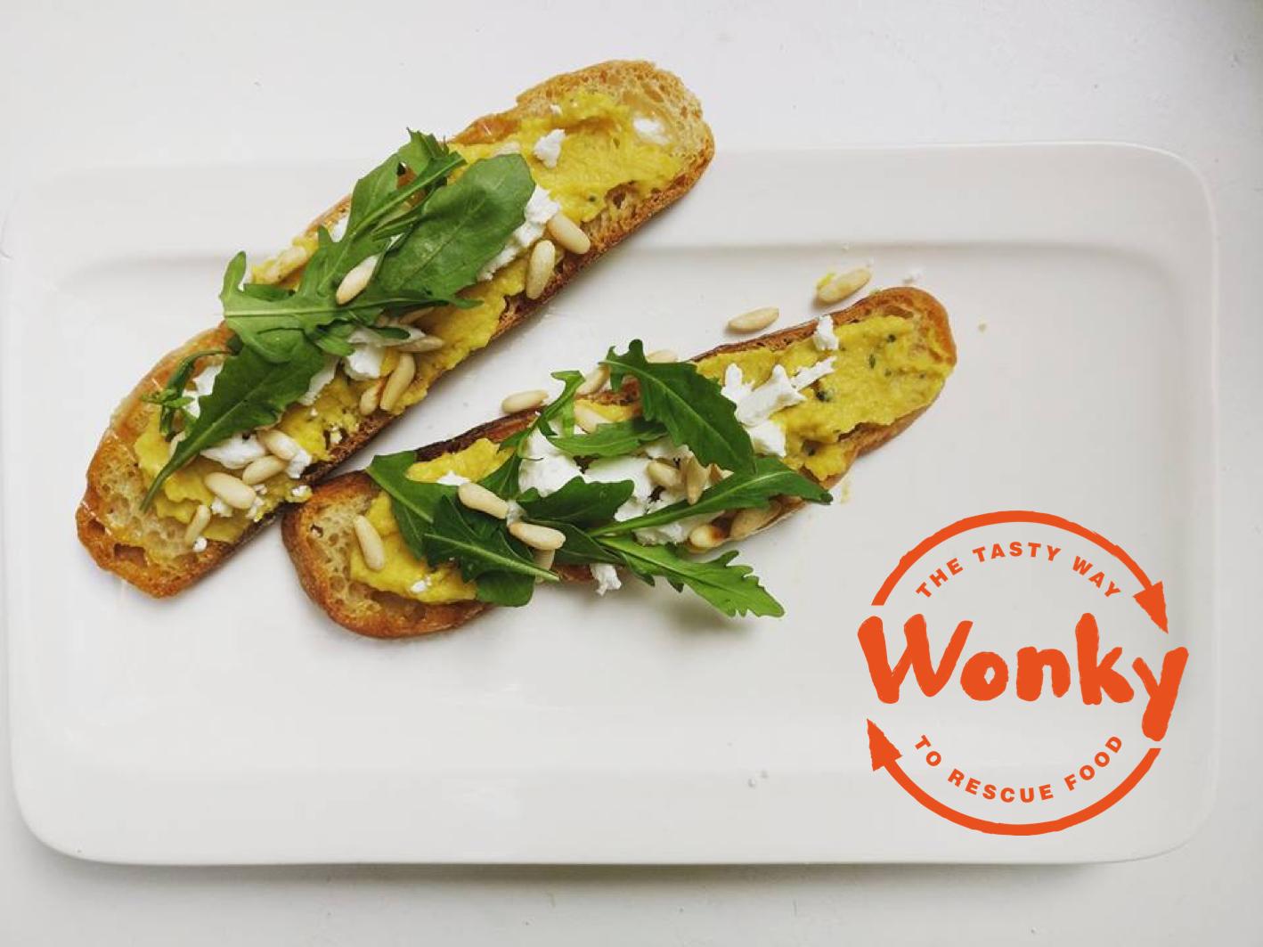 Foto van de Wonky toast met Wonky worteldip, geitenkaas, rucola en pijnboompitten