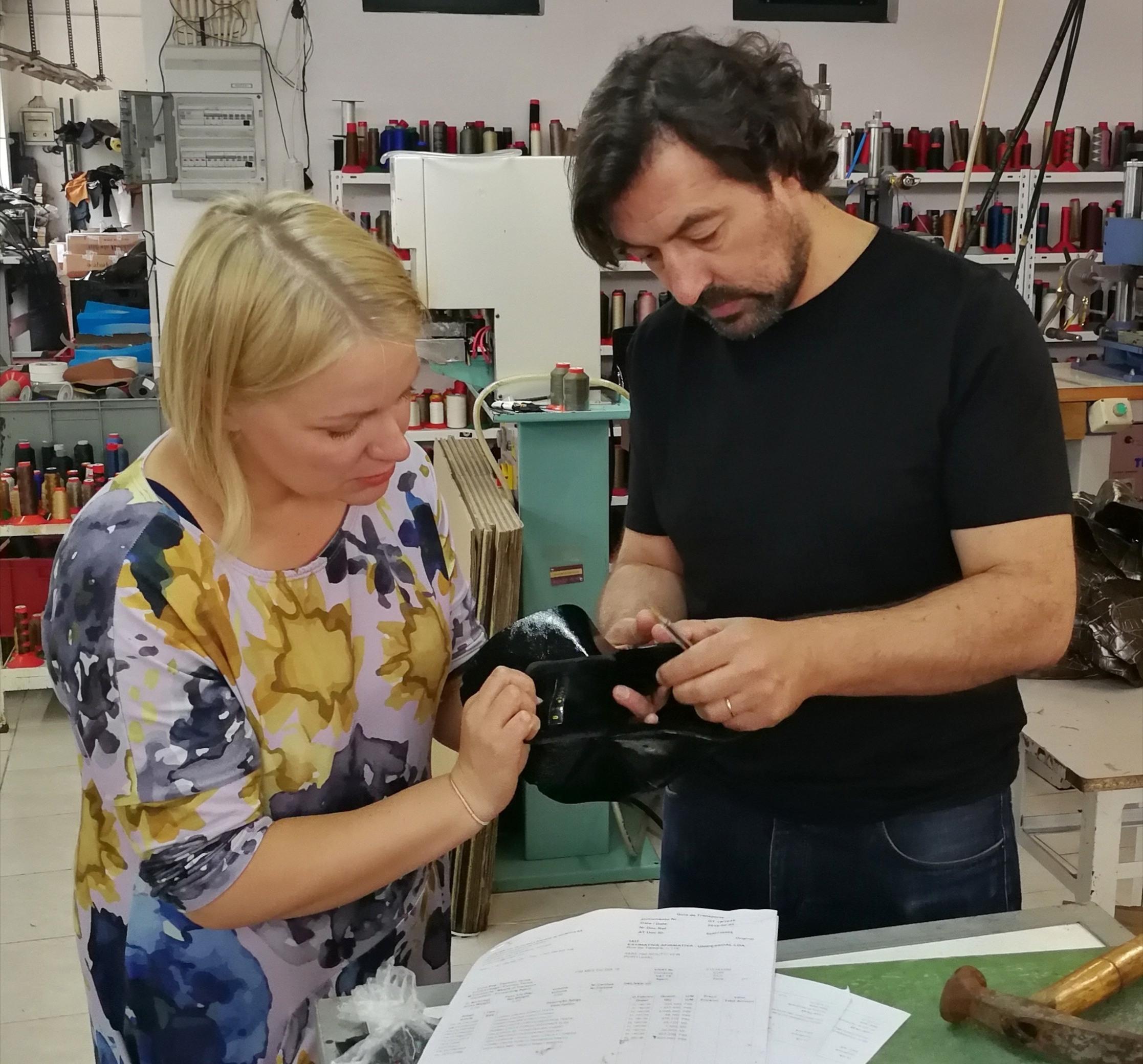 Vilma ja Joao tarkastelevat kengän päällisneulosta ennen lestille pinnaamista.