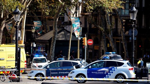 Policemen stand next to vehicles in a cordoned off area after a van ploughed into the crowd, injuring several persons on the Rambla in Barcelona.(JOSEP LAGO/AFP/Getty Images)