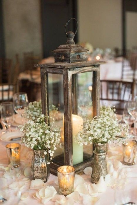 And here is my favorite. This beautiful winter wedding centerpiece combines rustic appeal with classic candles and subtle arrangements of flowers.