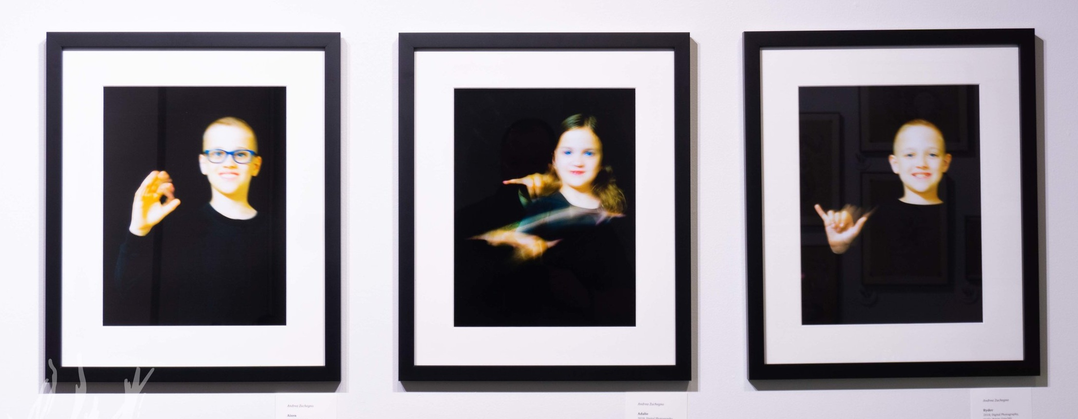 A photographic triptych by Andrea Zuchegno featuring her children's name signs.