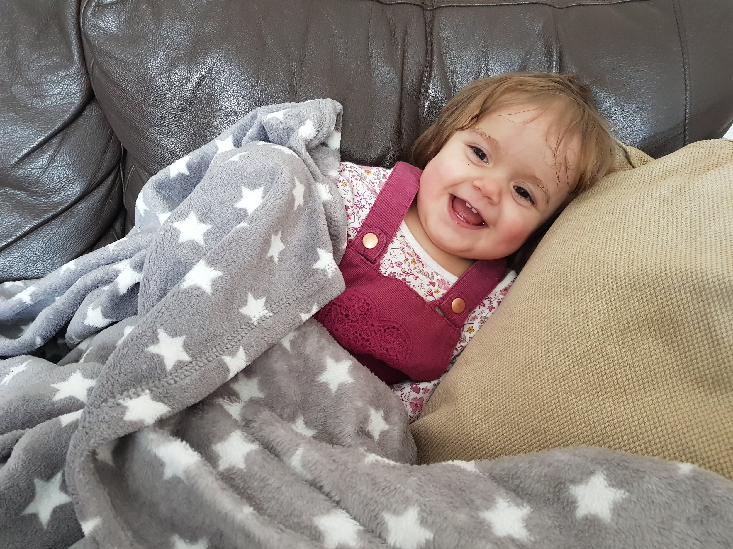 Cheeky baby snuggled up under an awesome blanket from Room to Grow