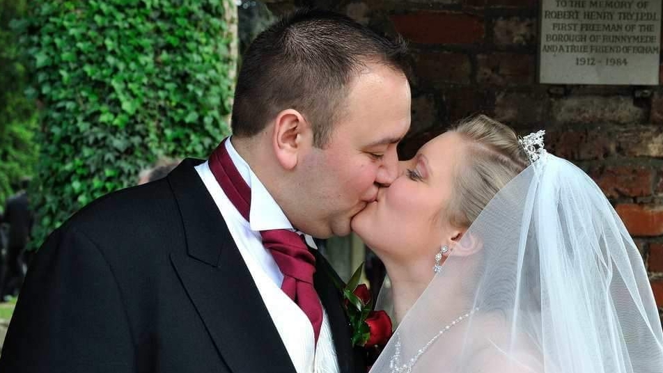 Kissing under the traditional entrance at St John's Church, Egham