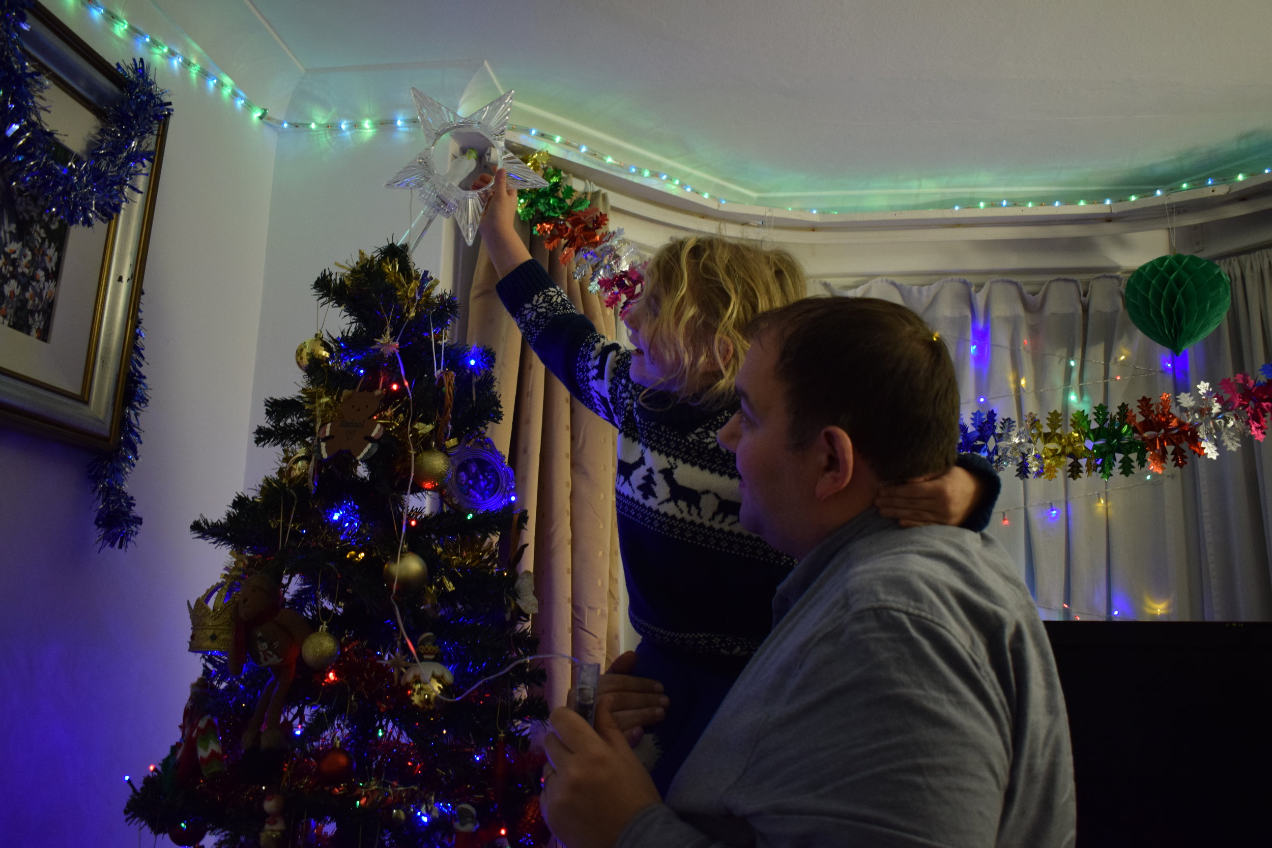 Putting the star on top of the Christmas tree
