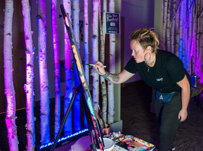 Artist Meg Rogers, curator for one of the pop-up galleries in Keene, paints at a Machina Arts event at The HIVE.