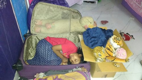 Niece Hiya, the inspiration behind  Kangaroo Kisses , hides in Nandana's suitcase at bedtime, surrounded by her animal toys