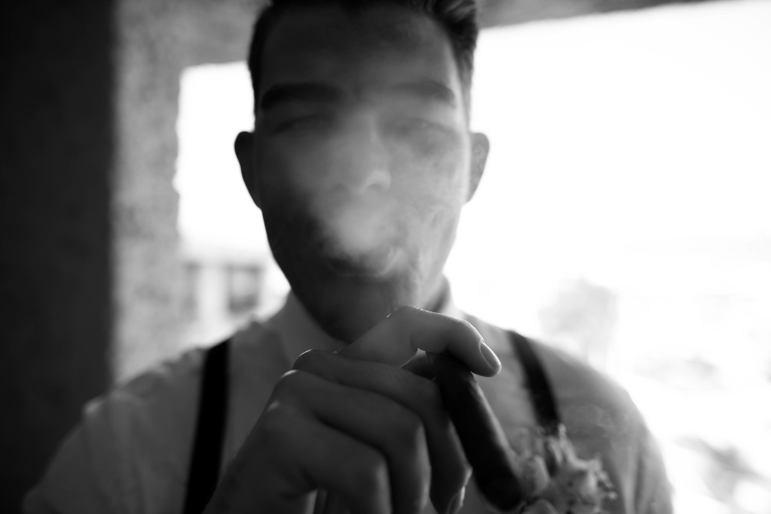 groom blowing cigar smoke. Edmonton.