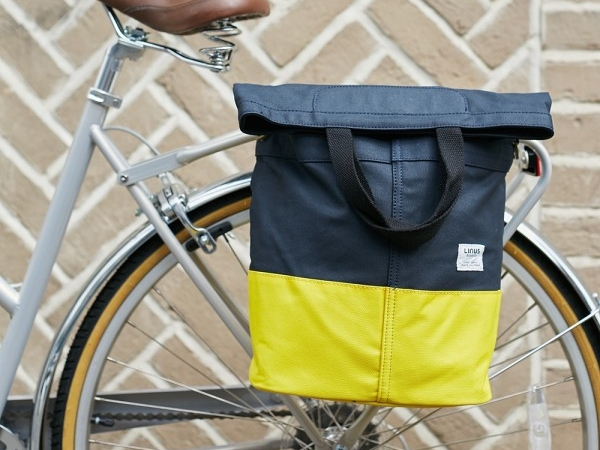 """Linus Sac Bike Pannier Bag Navy & Yellow  £49.99  Inspired by vintage boat bags, the block colour navy against yellow looks the business and delivers on performance too - providing a hefty 18L capacity once folded out, two hooks that clip onto your rack and a brass lock to secure your Sac to your bike. What really marks this bag out as unique is how it looks off the bike, thanks to an adjustable shoulder strap that transforms it into a stylish handbag. It's not just us who think it's bangin'. The Guardian says it's: """"The most stylish pannier we've ever seen""""."""