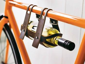 Bicycle Leather Wine Bottle Holder  £35  Wine! How we love thee so. If your go-to treat after a long day at work is a glass of pinot noir, you'll love this gorgeous leather bicycle wine carrier. Made in England from 100% vegetable tanned leather and brass, slide any standard wine or ale bottle in and snap shut. Cheers.