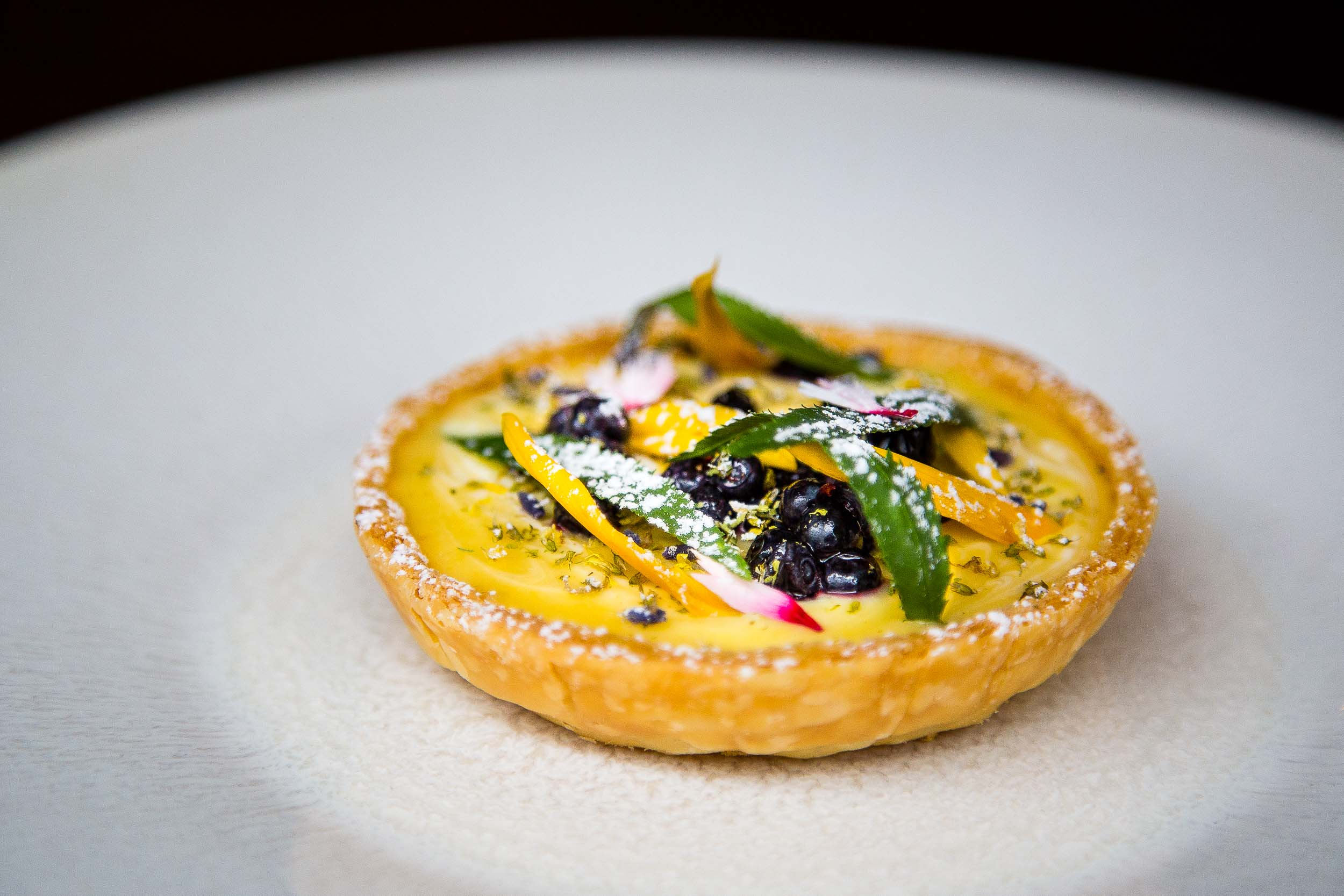 Lemon, Elderflower, and Creme Fraiche Tart with Wild Blueberries and Marigold Shoots
