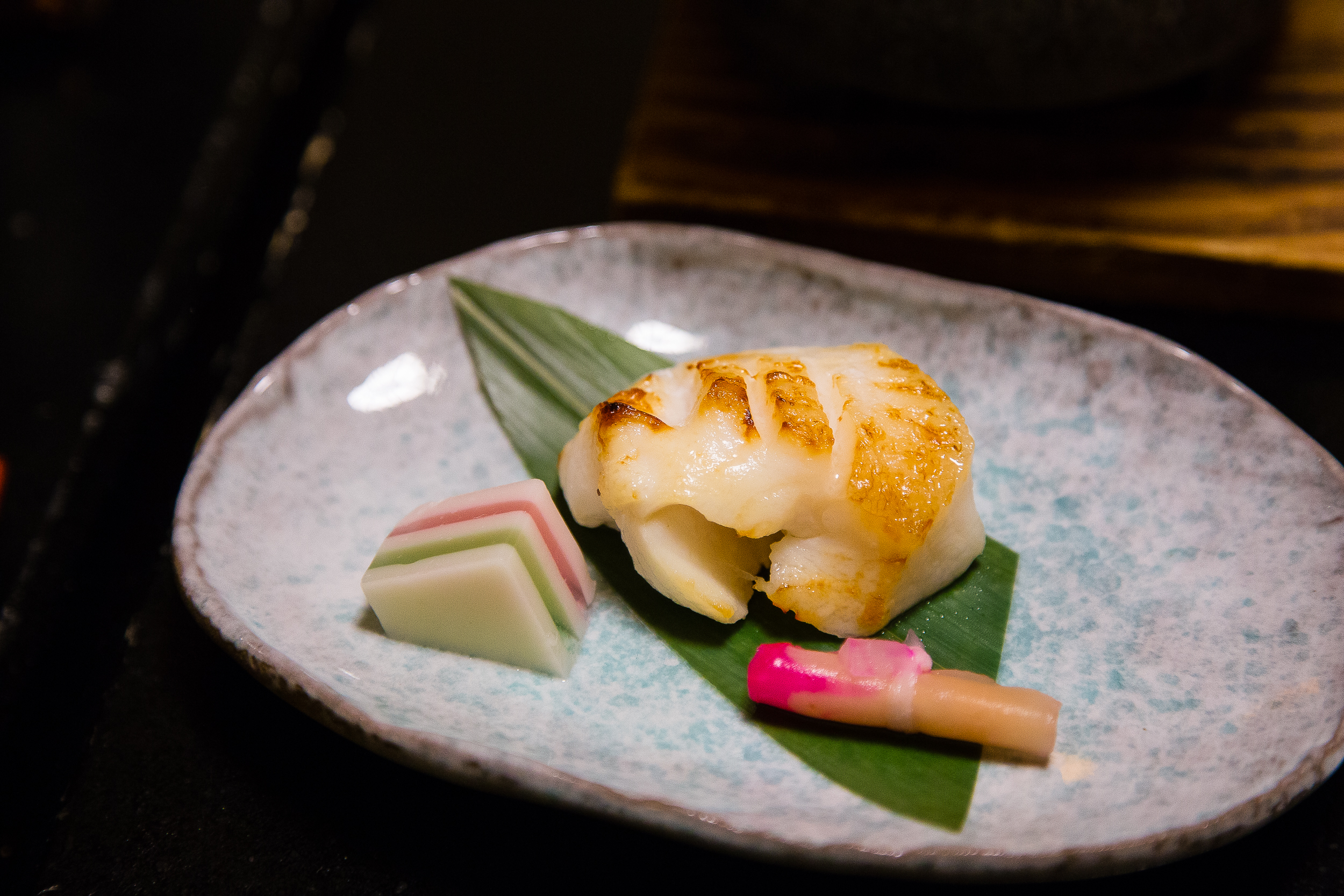 Unidentifiable fish with unidentifiable jelly substance and pickled ginger shoot