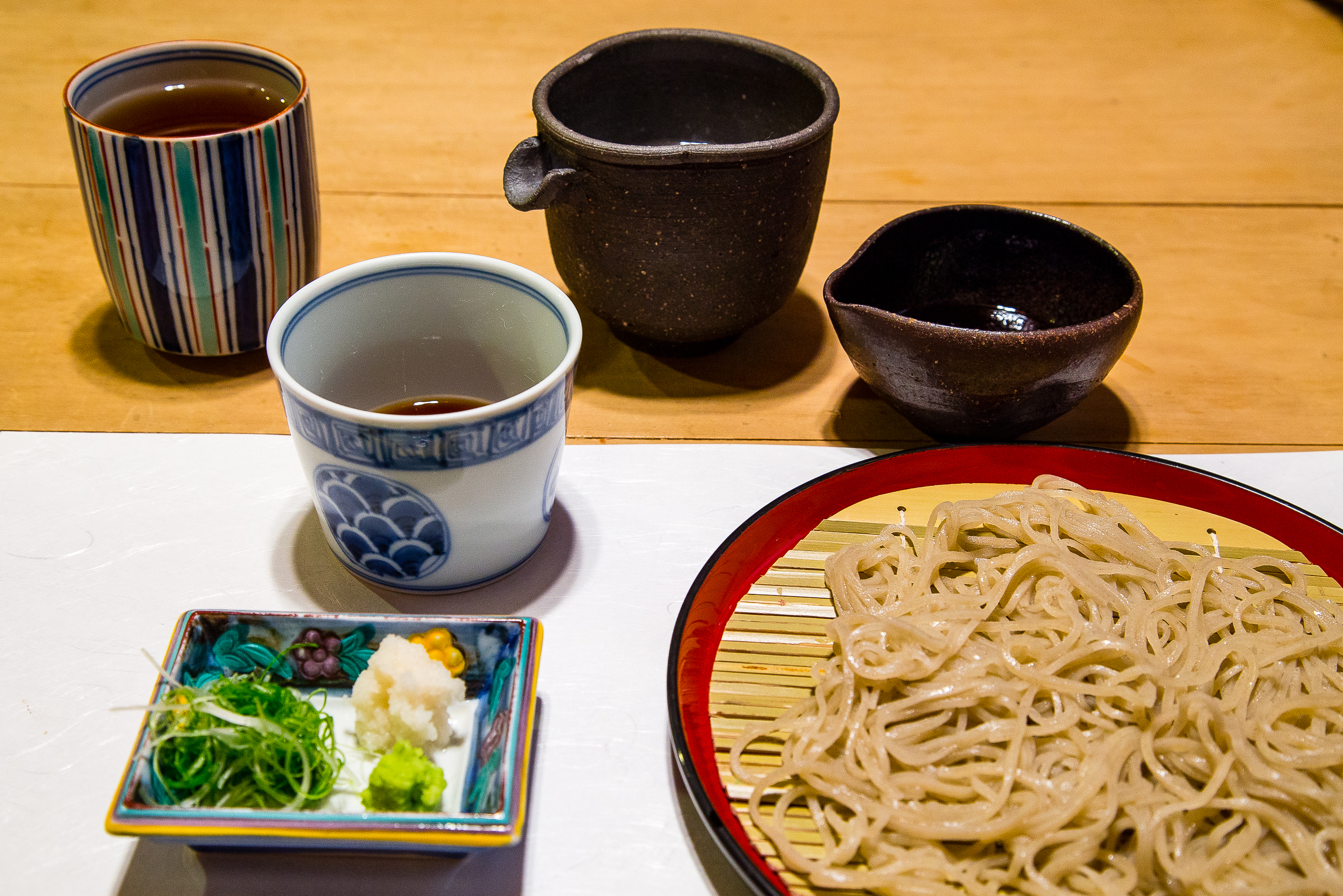 Soba course. From upper left corner: hot tea, dipping sauce, soba water, soy? sauce, toppings to add to dipping sauce.