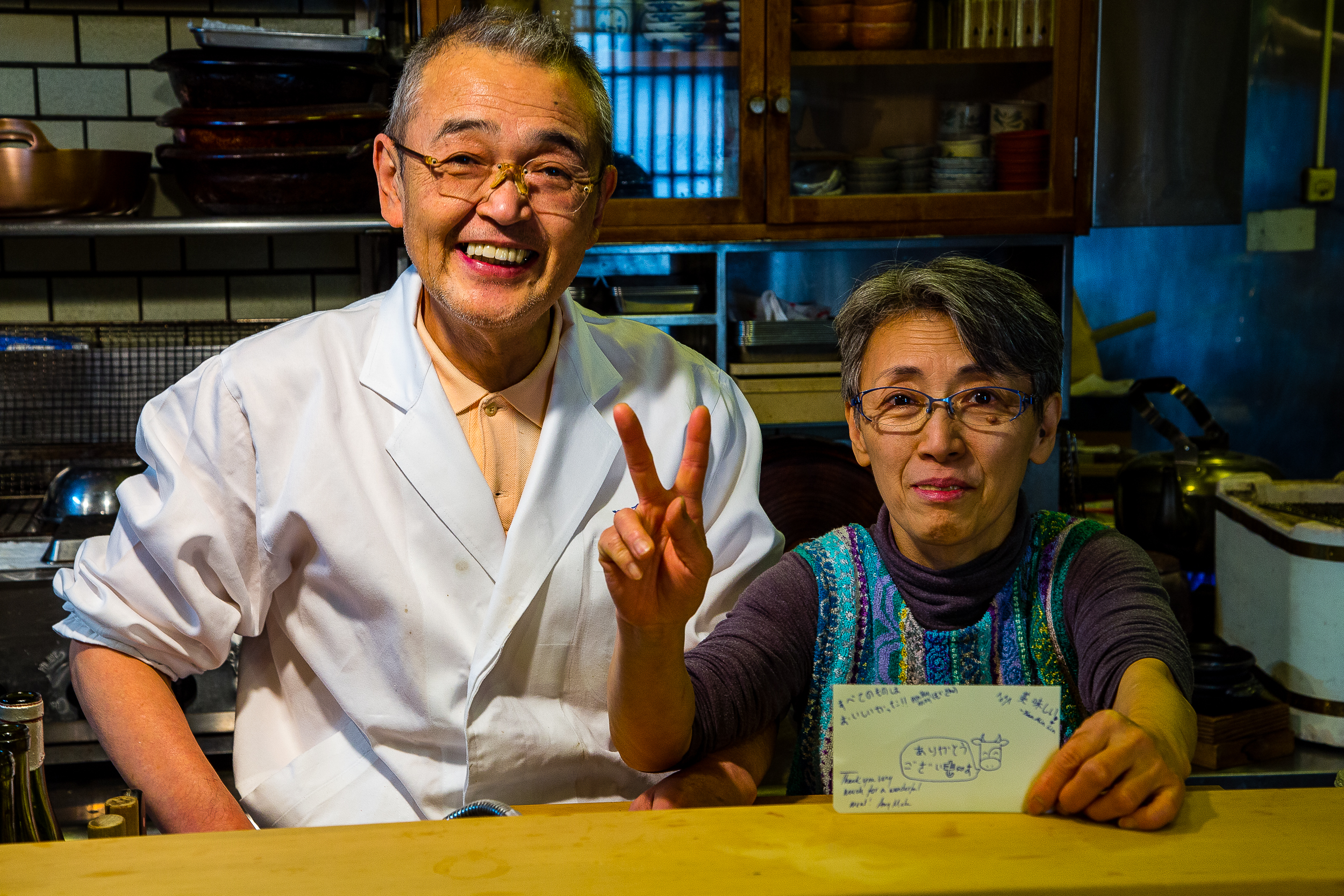 """The owners. Aren't they cute? They also single-handedly run the kitchen. For whatever reason, people love my cow drawings (I can't draw anything else), so I drew them a cow saying, """"ありがとうございもす""""."""