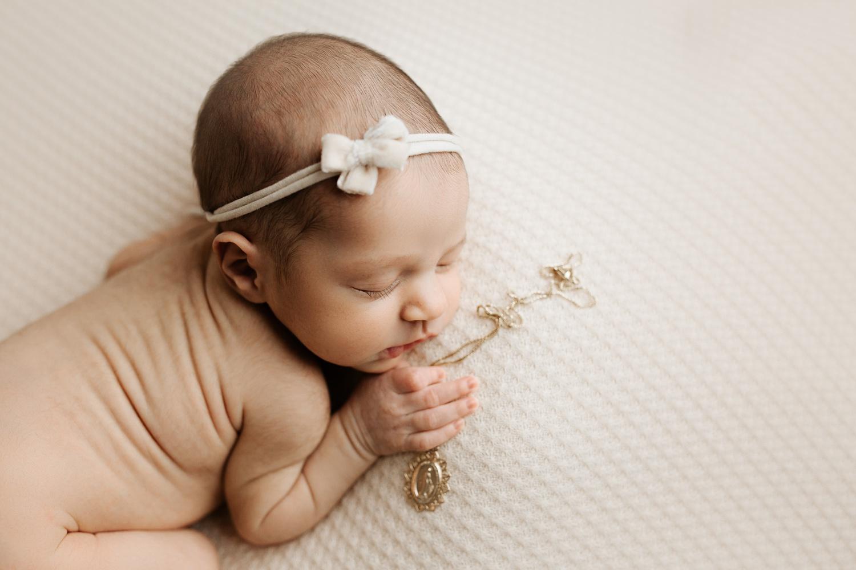 newborn girl holding great grandmother necklace
