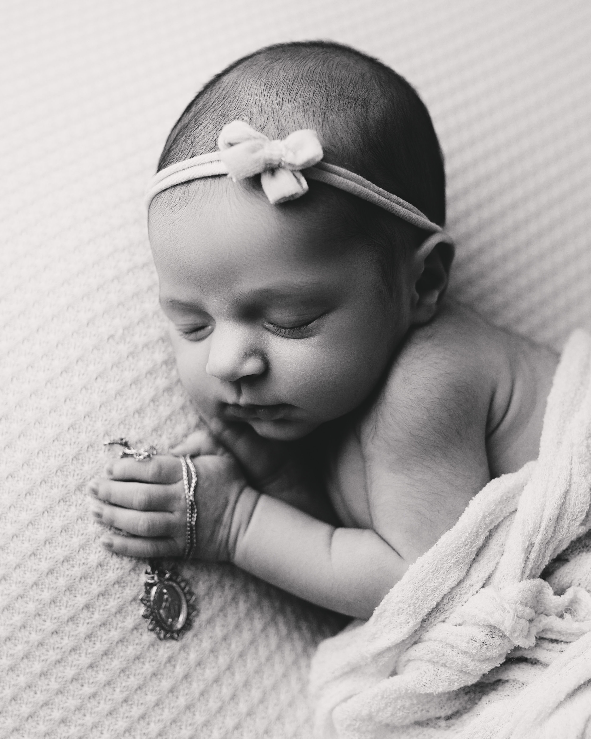 Newborn baby in Morristown NJ photo studio holding great grandmother necklace in black and white