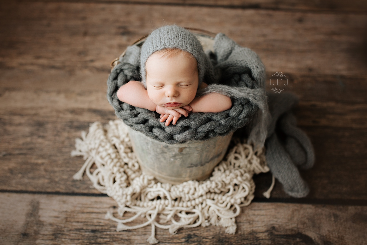 baby boy in a bucket posed in Lincoln Park NJ photography studio