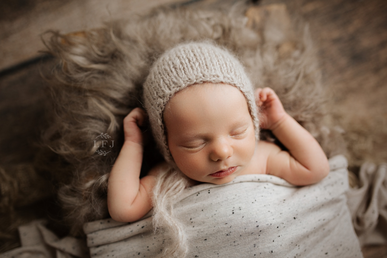 baby tucked in with knitted bonnet hat on rustic style setting