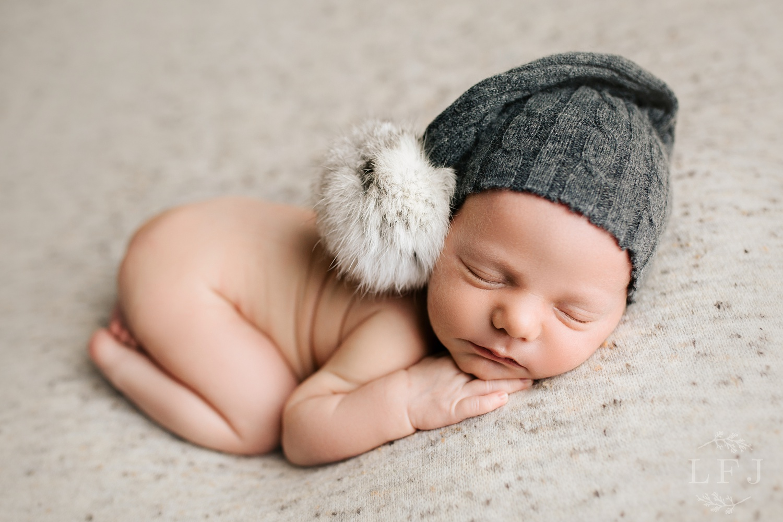 baby boy with gray pom pom hat posed tushy up