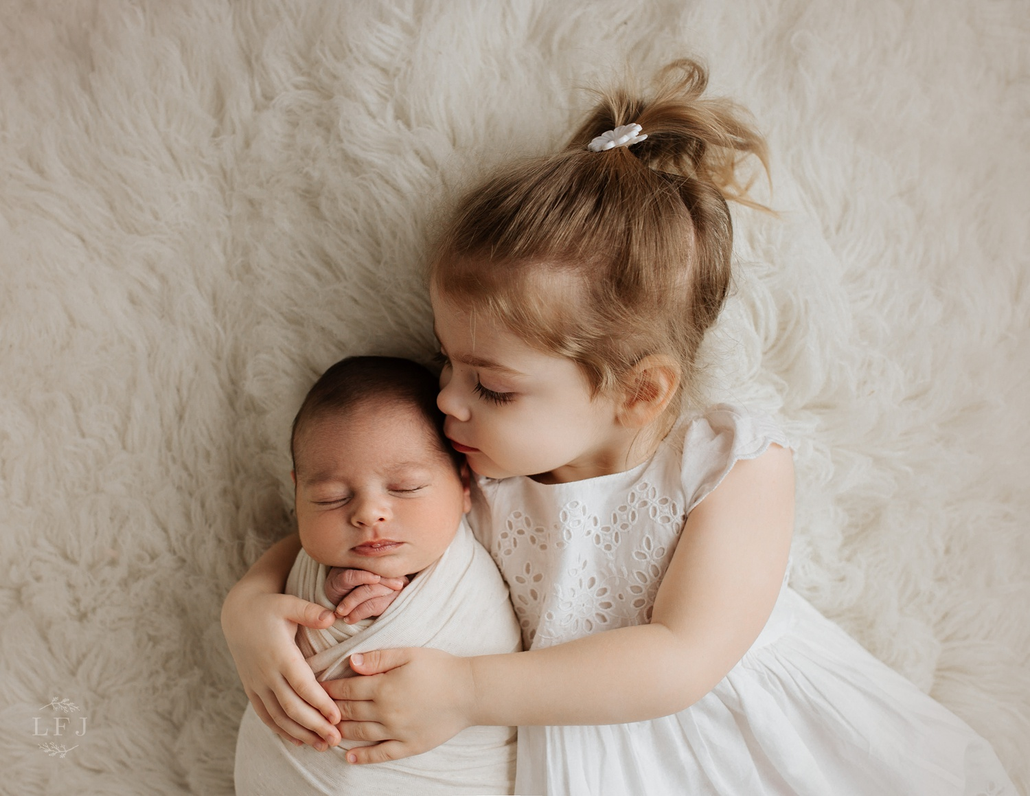 newborn Boy with toddler big sister kissing his forehead in Nj photography studio