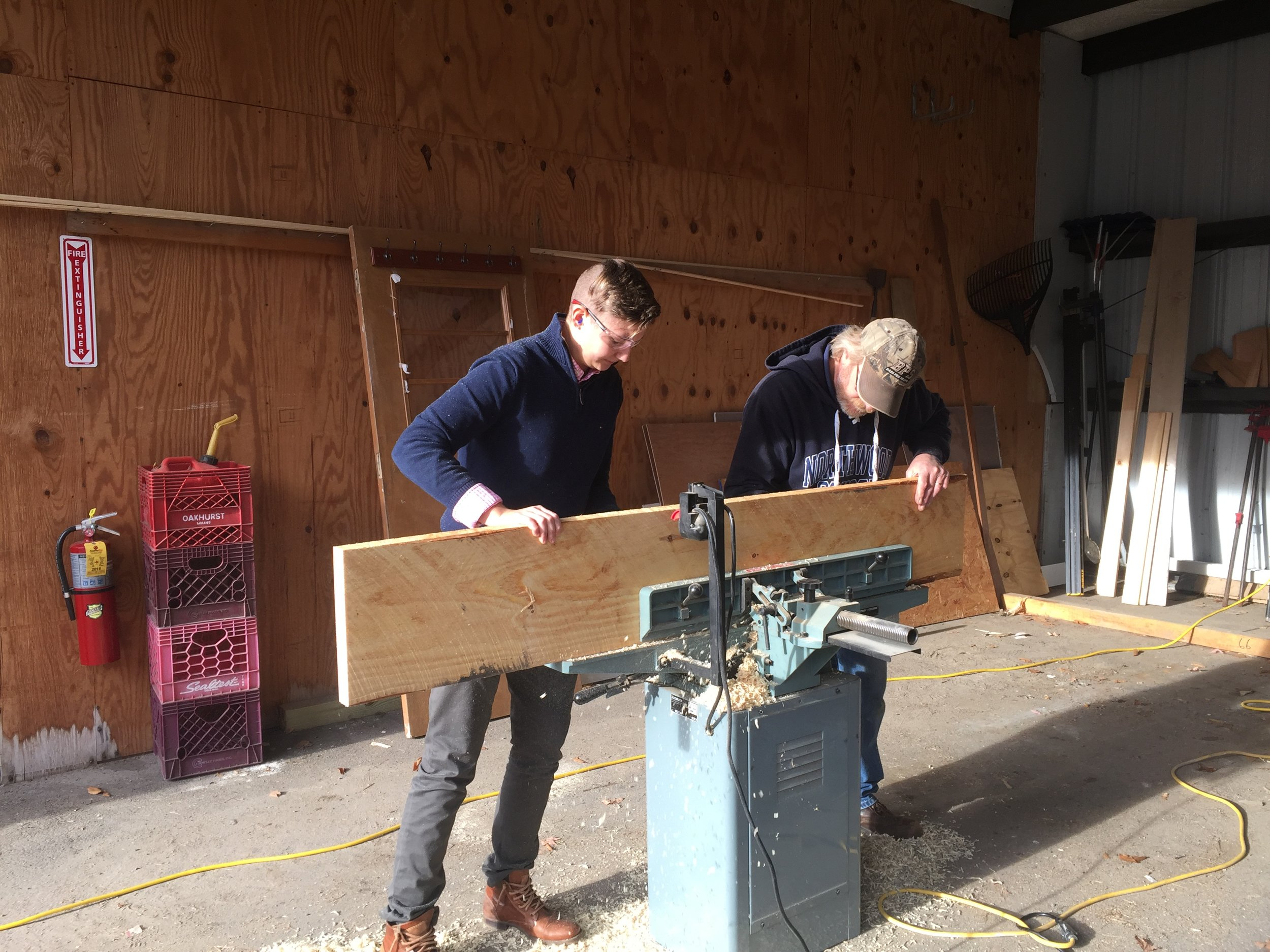 Hannah Rose learns how to plane the boards that would become the counter top on the center island tool organizer and workspace she helped design.