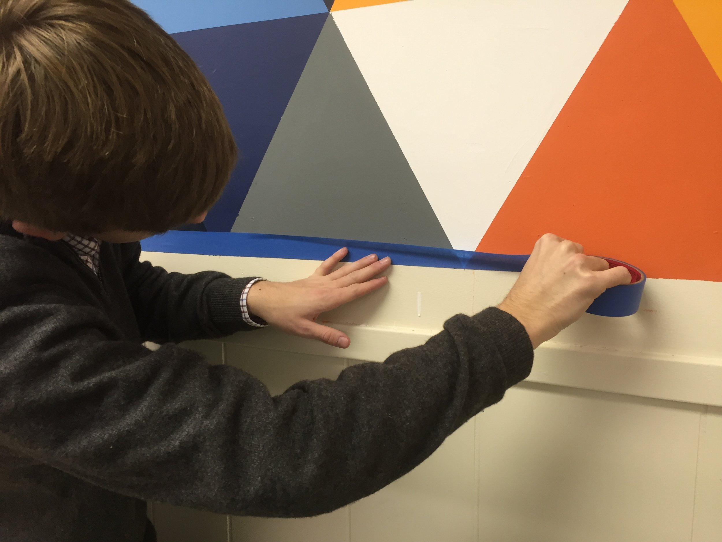 Ethan Bartlett works on a mural in the studio space.