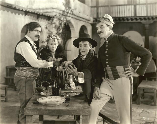 """From left to right, grouped around a table in a courtyard in a scene still from the 1922 silent comedy """"The Beauty Shop,"""" are the actors James J. Corbett, Louise Fazenda, Billy B. Van, and Montagu Love.  Courtesy   Wisconsin Center for Film and Theater Research. Used with permission."""