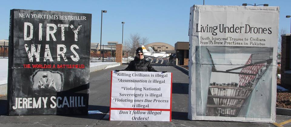 "Bev Rice at the March 19, 2015 ""Big Books"" anti-drone war protest at Hancock Air Base outside Syracuse, NY."