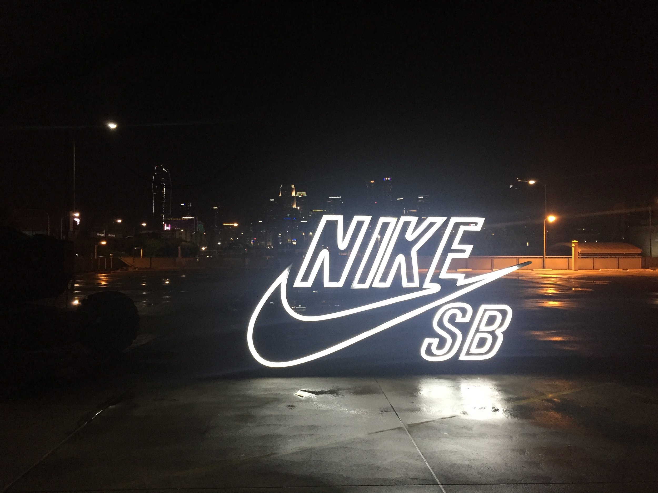 The big Nike SB signs seen in the spot are custom neon w/ channeled metal framing that were hung from cranes / condors and shot in-camera. The main one is 12' wide.