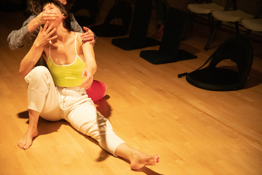 Photo by Intisar Abioto at New Expressive Works   This residency at Art Klub NOLA is supported by funds from the Oregon Arts Commission.   Two white femmes are dancing on a wood floor. One's body always overlaps the other's.