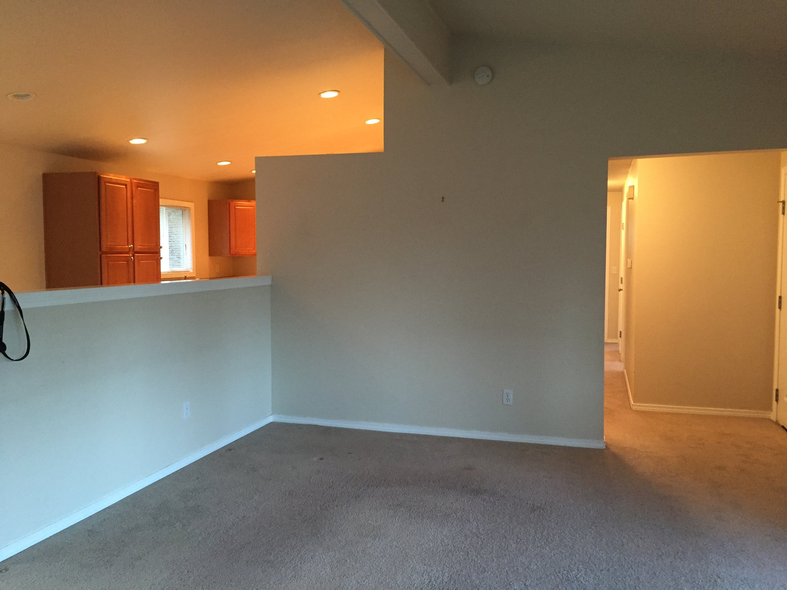 Living Room, Before: Look at all those strange walls and nasty carpet.