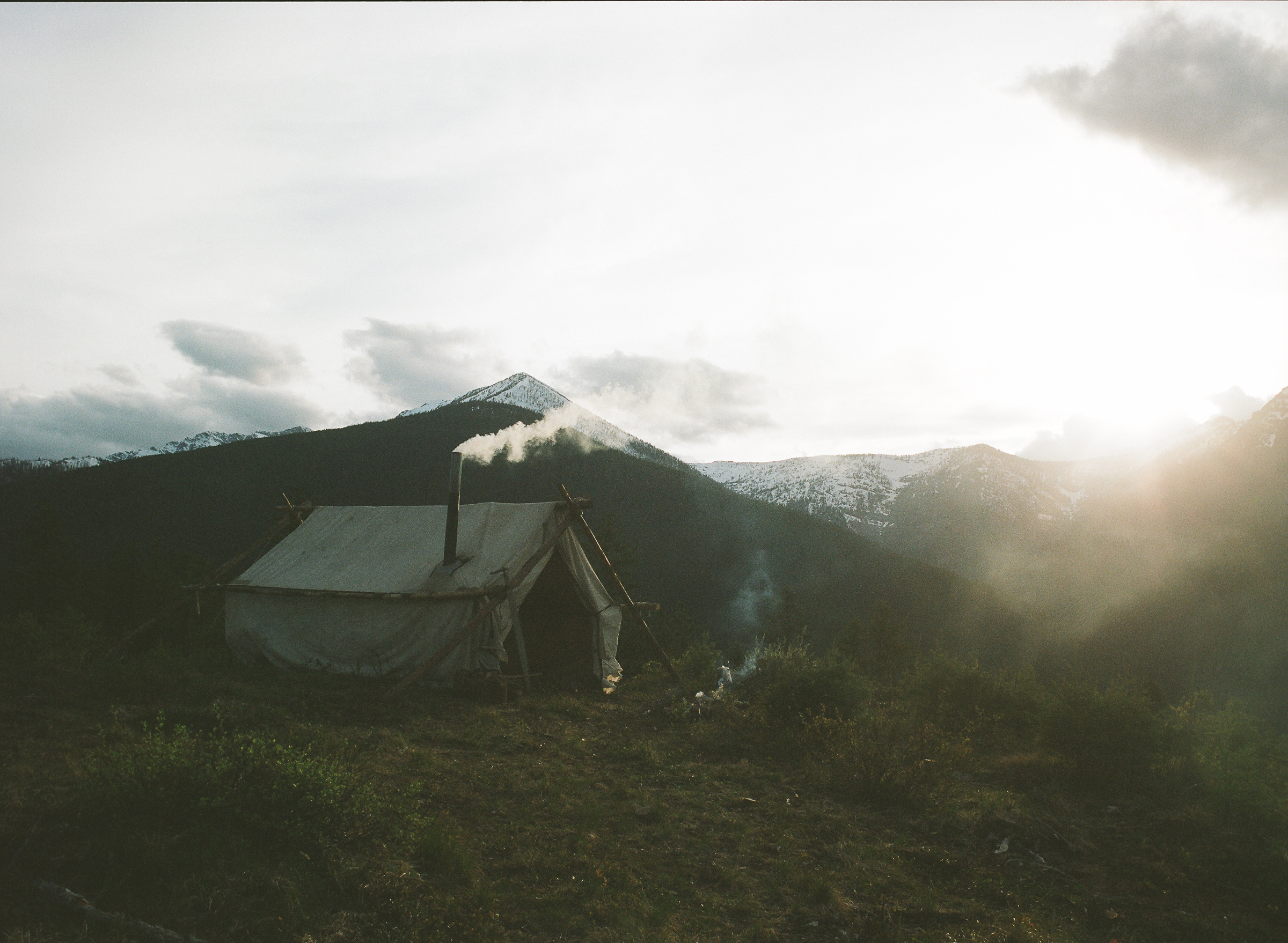 A hunter's wall tent billows out wood smoke in the backcountry of Montana.  Shot for Filson. © 2012 - 2016 C.C. Filson Co.