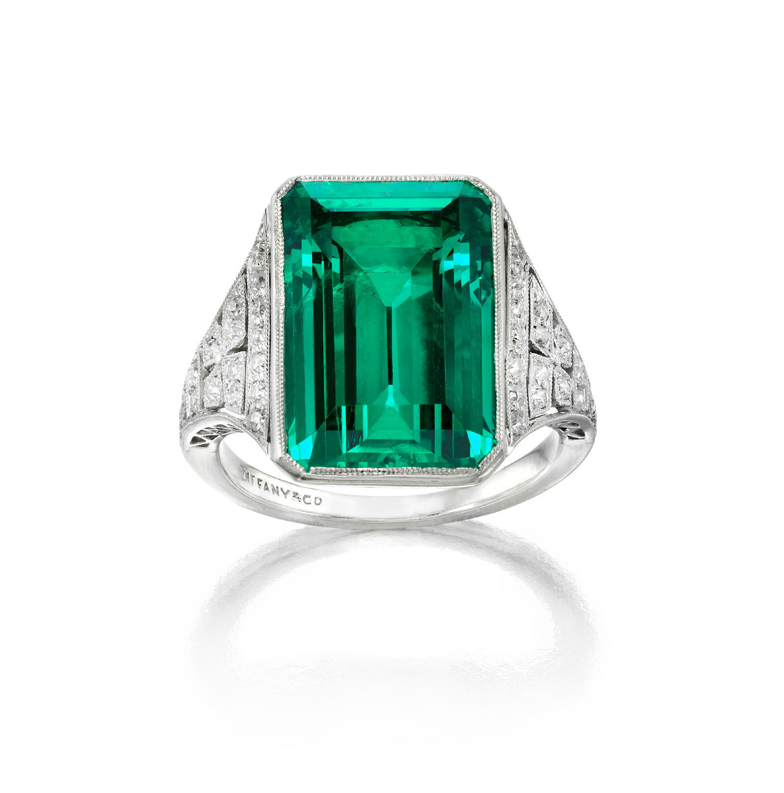 Art deco emerald and diamond Ring by Tiffany & Co., New York, circa 1925, for Helen Hay Whitney. Emerald-cut emerald in a millegrain bezel accented on the sides with old European-cut diamonds in millegrain settings, creating a four-leaf form. Mounted in platinum. 1 emerald, 8.51 carats; 34 diamonds, .50 carat.
