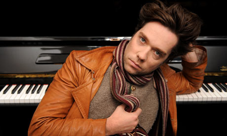 """EXAMINER.COM Interview: Rufus Wainwright        Rufus Wainwright , once referred to by Sir Elton John as """"the greatest songwriter on the planet,"""" has already established a reputation for not fitting neatly into any one prescribed genre. But his sixth studio full-length, """"All Days Are Nights: Songs For Lulu,"""" a piano-centric concept album released in spring of this year, propels him even further into the realm of the unclassifiable. Wainwright, a prominently portmanteau performer, opts for the minimalist route, reasoning that less instrumentation is more.   However, that doesn't mean the album is stripped down or easy. Quite the contrary. Wainwright instead experiments with the interplay between the simplicity of an unadulterated vocal line and the complexity of piano lines that tranquilly ripple and tumultuously surge their way through a near 50-minutes of soul-bearing compositions.   Just like with any album, Wainwright struggled with writing many of the songs, and he cited """"The Dream"""" as one of the numbers that was """"more laborious"""" than the others. However, surprisingly, a good number of tracks, including """"Zebulon,"""" """"Sonnet 20"""" and """"Martha"""" came to him rather easily.  """"Those are songs that came in a fraction of an instant and practically wrote themselves,"""" he shared. """"I didn't really have to work much to get them. That is always a good sign. It's a very rare and very cherished moment for any artist.""""  Audience members on this tour will be exposed to a Wainwright as he has never been before. While he is known for his telling lyrics that unabashedly tackle personal issues pertaining to relationships, strained family dynamics and drug addiction, """"All Days Are Nights"""" takes honesty to a new level–one where not just the subject matter is candid, but the arrangements are as well.  """"A lot of it has to do with the arrangements,"""" he shared. """"When you're down there and you're just working with the black and white keys, it really draws out a certain truth within you and you """