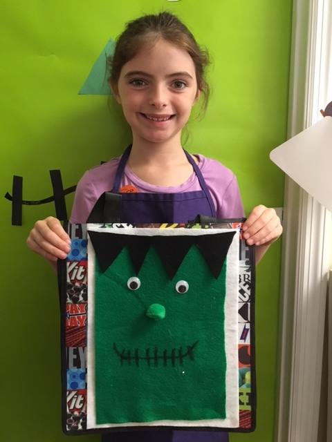 A camper shows off her trick-or-treat bag
