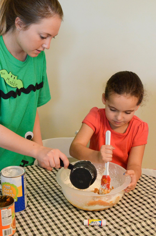 Miss Maddie helps a camper mix up pumpkin play clay